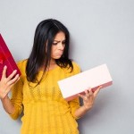 42455716 - unhappy young woman holding gift box over gray background